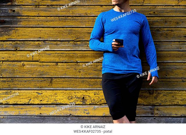 Close-up of athlete leaning against house wall holding cell phone