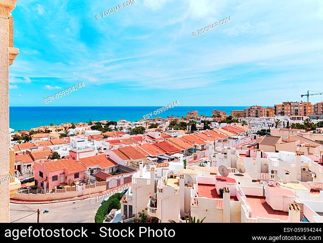 Above view rooftops of spanish pretty residential houses near the Mediterranean Sea, turquoise water, horizon over the sea, clear blue sky in Torrevieja