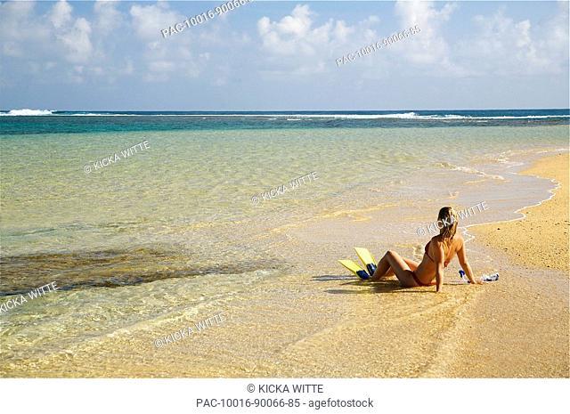 Hawaii, Kauai, Tunnels beach, A woman wearing yellow and blue fins on beach
