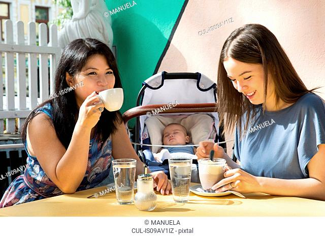 Young woman with mother and baby daughter drinking coffee at sidewalk cafe