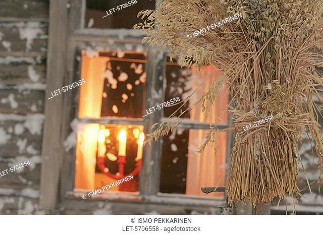 An oat sheaf for birds, a candelabrum burning on a window sill  Outokumpu, Finland