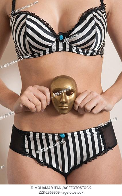 Close up of a young woman wearing lingerie holding a metal mask