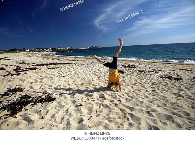 France, Bretagne, Finistere, Trevignon, Girl doing cartwheel on beach