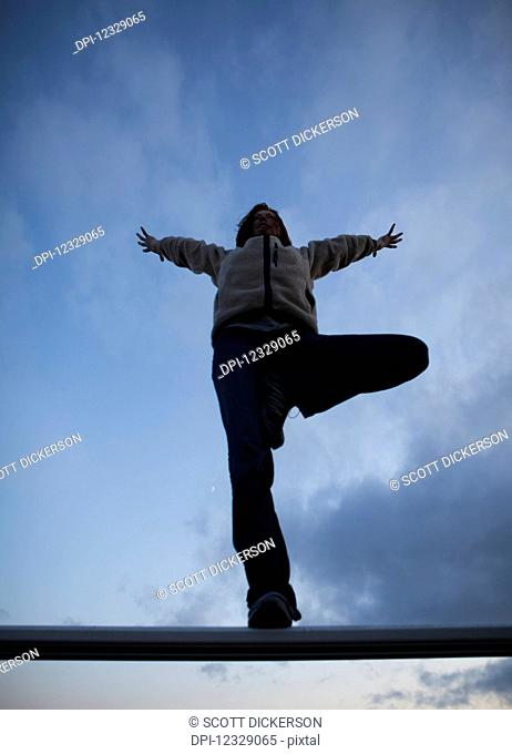 Low Angle View Of A Woman Doing A Yoga Pose On A Beam With Blue Sky And Cloud; Alaska, United States Of America