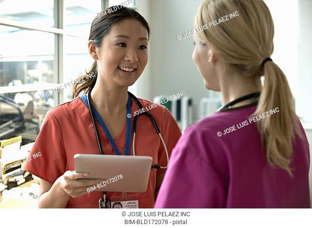 Nurses using digital tablet in hospital room