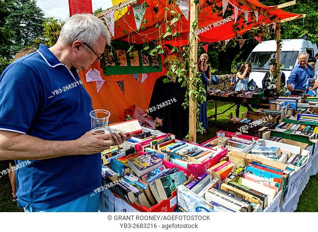 A Man Chooses Secondhand Books From The Bookstall At The Medieval Fair Of Abinger, Surrey, UK