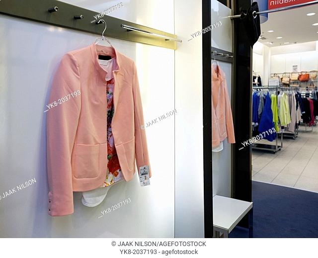 Woman`s jacket hanging in dressing cabin, reflection, mirror. Retail store, shop, shopping