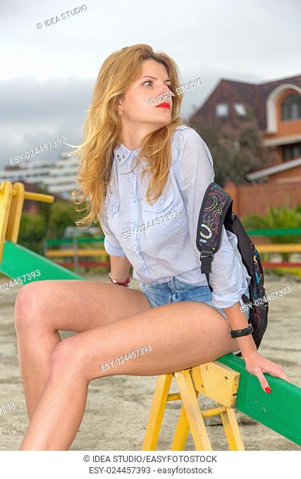 Portrait of young beautiful woman in shorts with backpack
