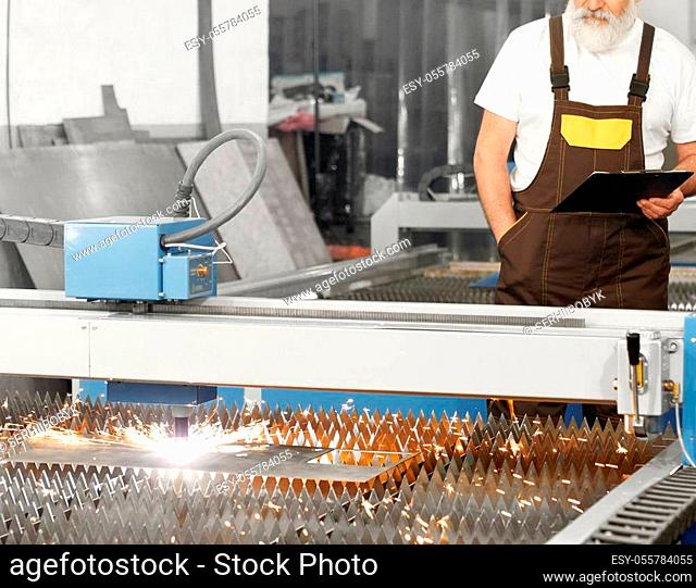 CNC laser plasma cutting metal, sparks. Engineer standing behind and observing process of plasma torch cutting steel sheet
