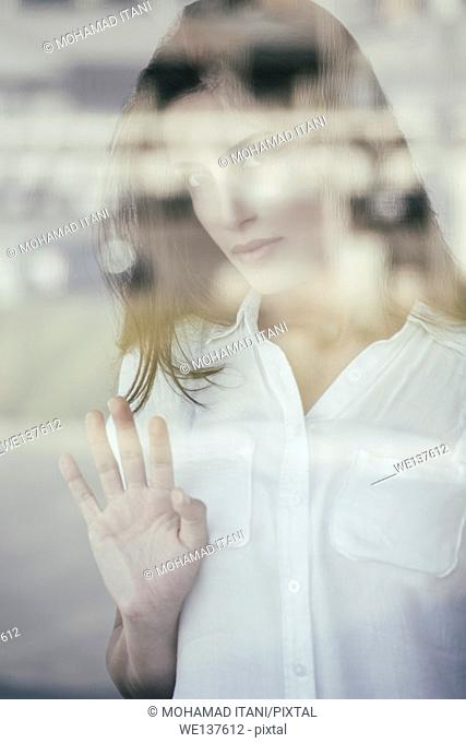 Sad young woman looking out of the window
