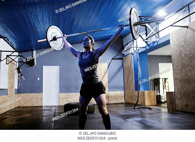 Woman lifting barbell in gym