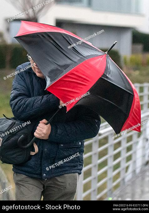 """16 February 2020, North Rhine-Westphalia, Dortmund: A walker with an umbrella fights with the wind at Lake Phoenix. The foothills of the hurricane """"""""Victoria""""""""..."""