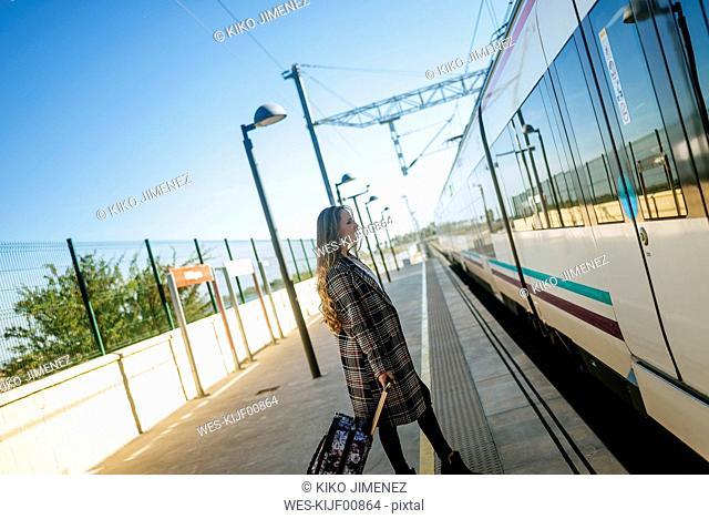 Woman walking towards a train car at a station