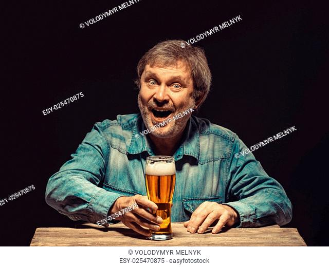 Enjoying his favorite beer. The front view of handsome smiling man as fan in denim shirt with glass of beer, sitting at the wooden table