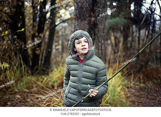 Child plays with a bow in the woods