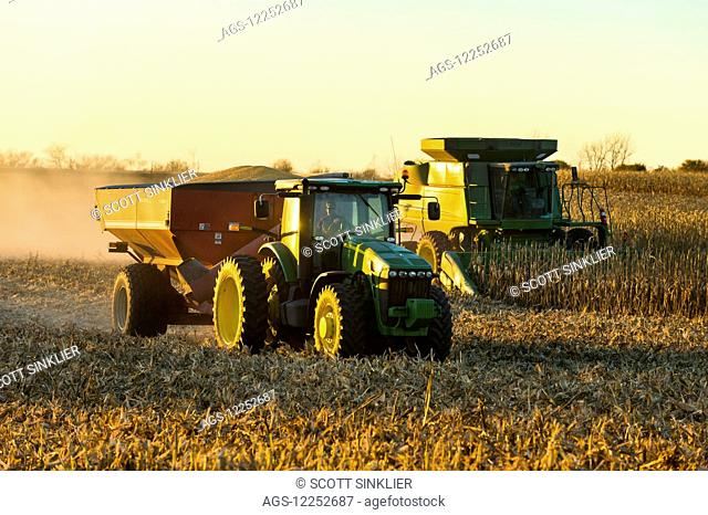 A farmer harvests yellow grain corn with his John Deere combine at dusk in Southern Iowa while a full grain wagon heads to the storage bin; Iowa
