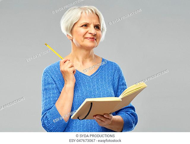 senior woman with pencil and diary or notebook