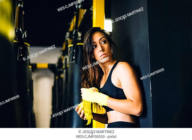 Female boxer bandaging her hands in a gym