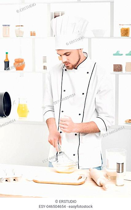 Chef man in uniform makes dough in the kitchen