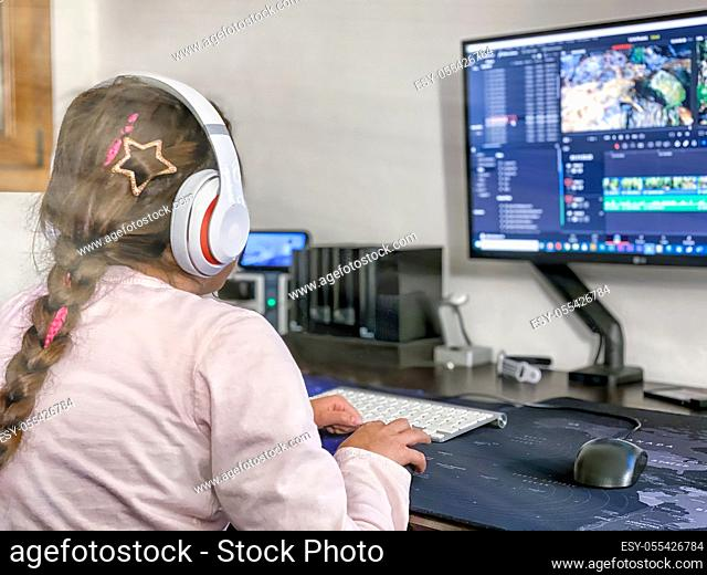 Young influencer youtuber girl editing footgae video file on the computer