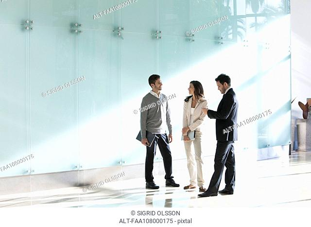 Business associates chatting in office corridor
