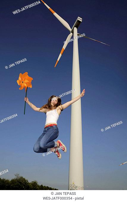 Germany, North Rhine Westphalia, Neuss, female teenager at wind farm jumping in the air with windmill in her hand