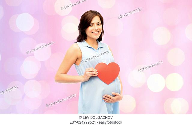 pregnancy, love, people and expectation concept - happy pregnant woman with red heart shape touching her belly over rose quartz and serenity holidays lights...