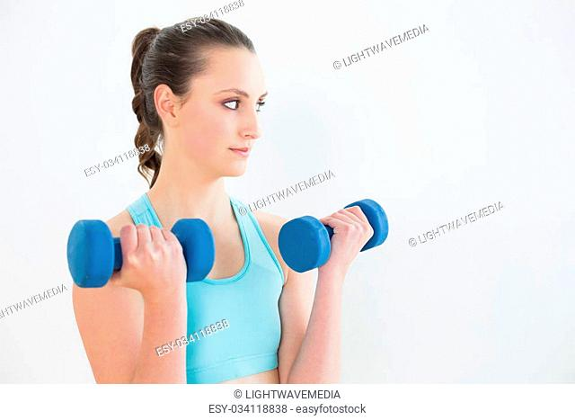Serious young woman with dumbbells against wall at fitness studio