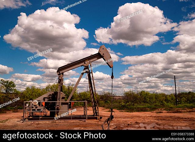 A dramatic sky surrounds this oil pump jack in a muddy bog in the united states
