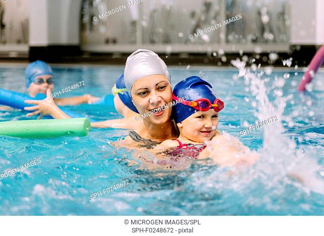 Swimming class. Instructor working with little girl