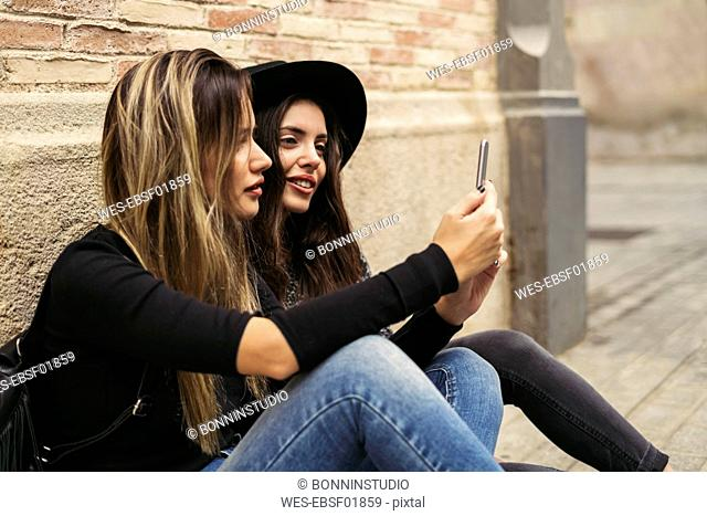 Two best friends sitting on the ground looking at smartphone