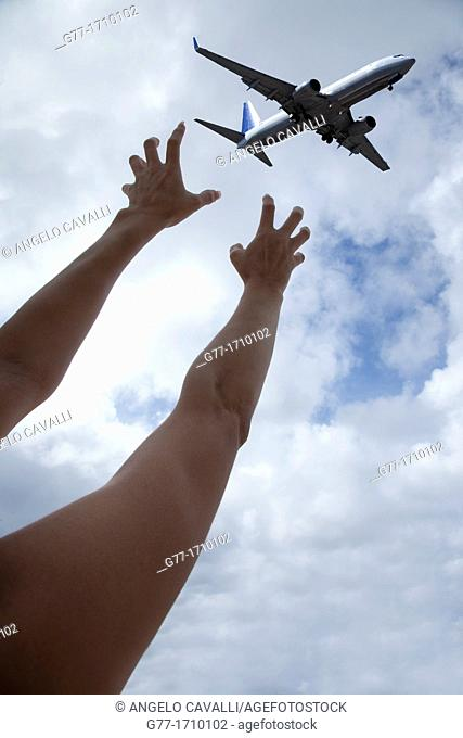 Woman's hand grabbing an airplane