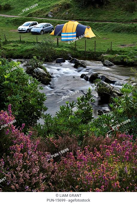 Tent situated in the Doone Valley in summer, pitched for camping beside the river, North Devon, United Kingdom