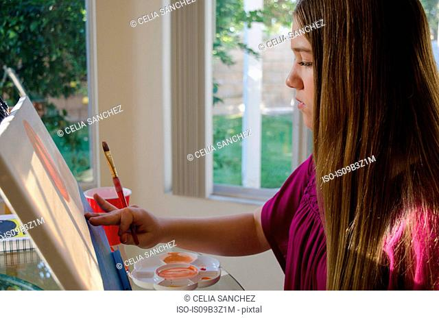 Teenage female artist painting on canvas in conservatory