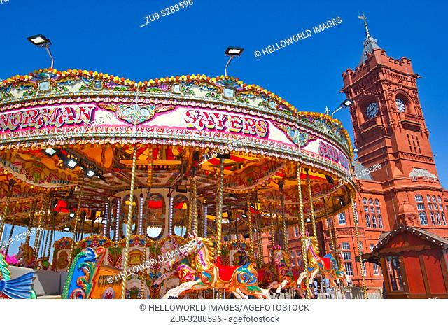 Fairground carousel ride and tower of the Grade 1 Listed Pierhead Building (Adeilad y Pierhead), Cardiff Bay, Wales, United Kingdom