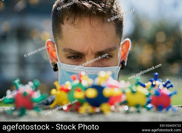 Caucasian guy with a protective mask and looking at virus models. The concept of Coronavirus