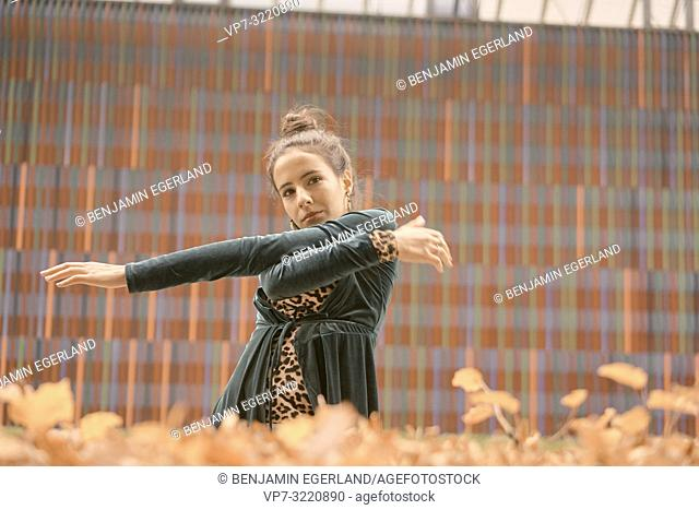 fashionable woman moving and dancing with hands, balanced, equated, balanced, in front of geometrical line pattern, in Munich, Germany