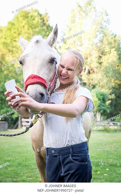 Girl taking photo with horse