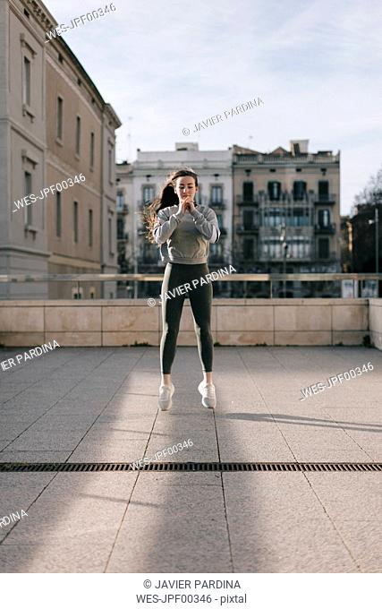 Young woman doing workout on terrace jumping in the air