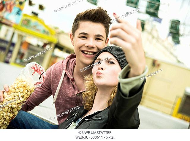 Teenage couple with popcorn photographing themself at fun fair