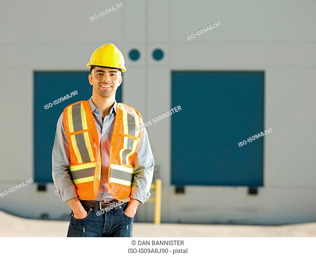Mid adult construction worker with hand sin pockets, portrait