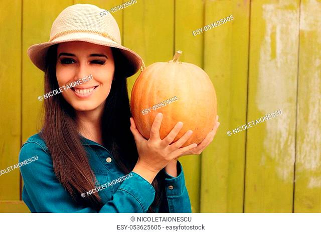 Denim girl wearing a hat and holding a fresh squash