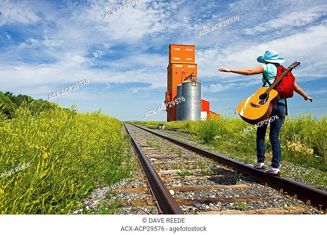 18 year old girl with guitar walking along railway with abandoned grain elevator in the background, Carey, Manitoba, Canada