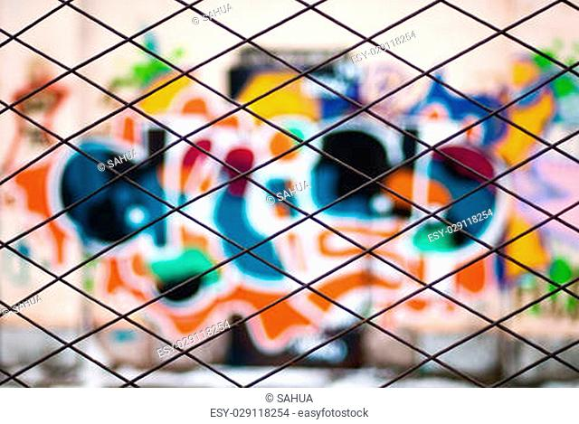 view to abstract blurred graffiti through metal bars fence
