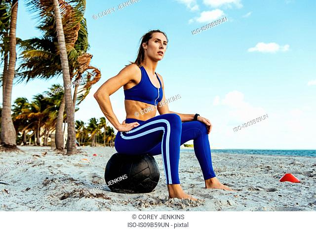 Young woman training, sitting on exercise ball taking a break at beach