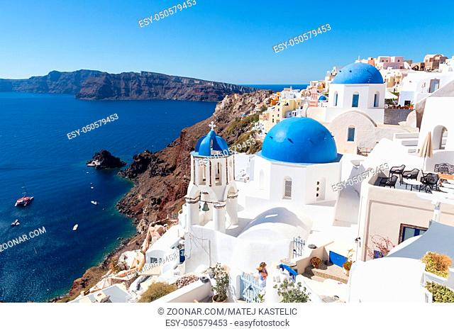 Cityscape of Oia, traditional greek village with blue domes of churches, Santorini island, Greece