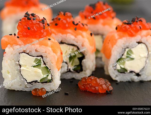 Philadelphia sushi with red caviar on a black slate board, close up