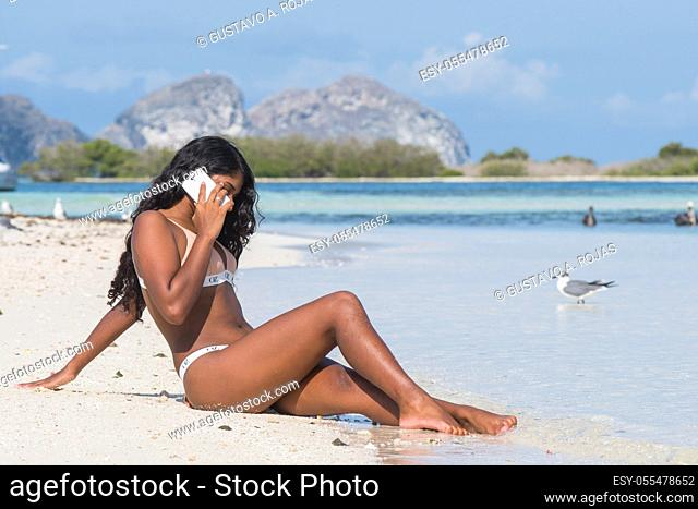 Beautiful young woman talking on the mobile phone in the tropical beach