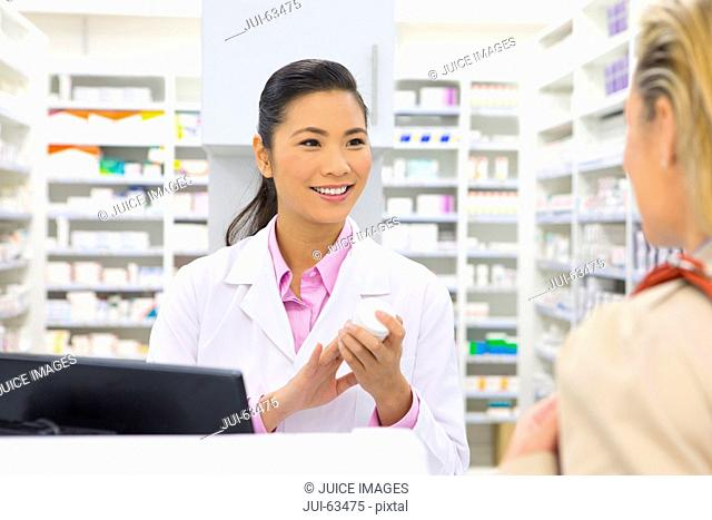 Pharmacist holding medication pot, smiling at customer from behind pharmacy counter