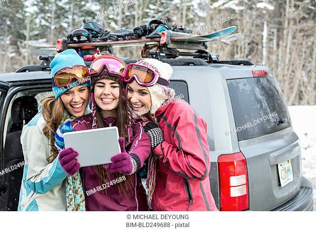Women posing for cell phone selfie in winter using digital tablet